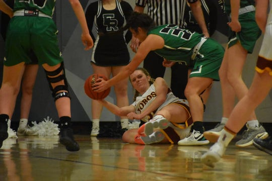 Rocky Mountain's Ashley Gilbertson tries to pass the ball while Fossil Ridge's Jazi Barela defends in the Sabercats' 54-23 win over the host Lobos on Feb. 21, 2020.