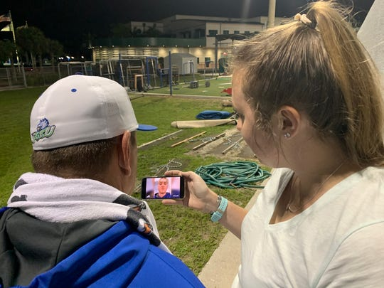 FGCU baseball coach Dave Tollett (left) and FGCU sports information director Meg Ellis (right) share a moment together, watching a video of former Eagle players wishing Tollett congratulatory messages following a 2-0 victory over Kent State. It was Tollett's 600th career win.