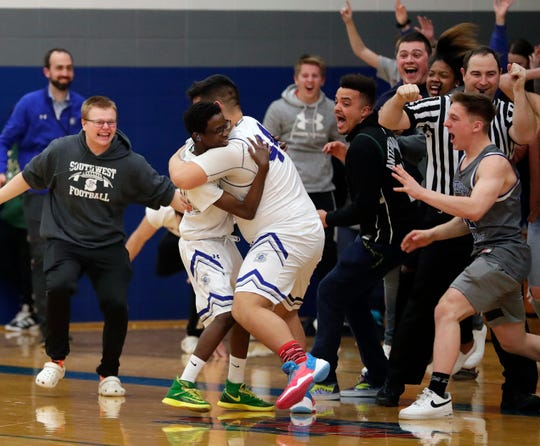 Green Bay Southwest senior Musa Abdikadir (33) is hugged by Grant Skenandore (44) and swarmed by fans after hitting a 3-pointer at the buzzer on Senior Night during a game against De Pere on Friday.