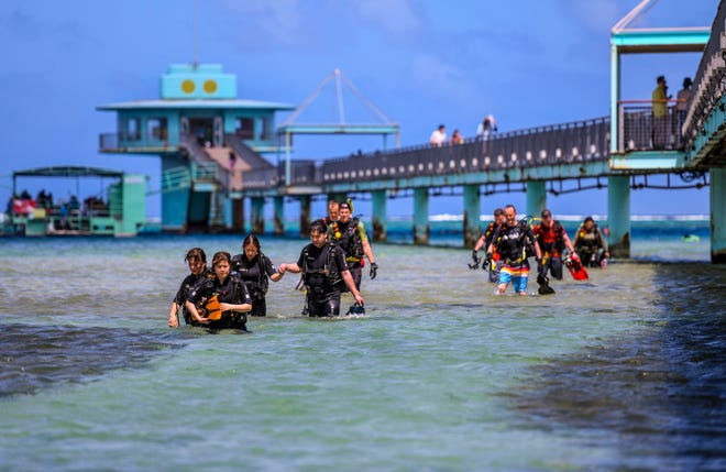 Scuba divers emerge from a morning of diving in the water near the Fish Eye Marine Park in Piti on Saturday, Feb. 22, 2020.