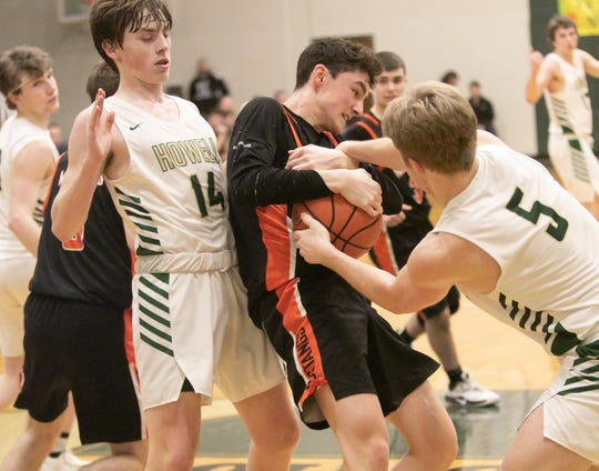 Howell's Peyton Ward (5) tries to rip the basketball from Northville's Max Barnes, while Howell's Bobby Samples backs up on Friday, Feb. 21, 2020.