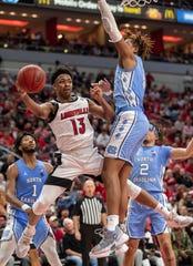 David Johnson of Louisville looks to pass against North Carolina's Armando Bacon at the YUM Center on Feb. 22, 2020