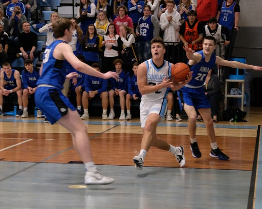 Lansing Catholic senior and captain Zach Gillespie (22) drives to the basket against Ionia Friday, Feb. 21, 2020. Ionia won by a basket 61-59.