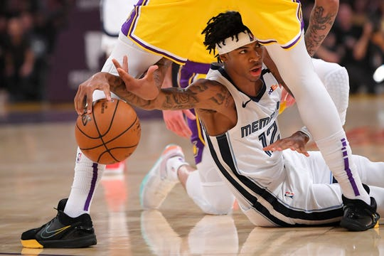 Memphis Grizzlies guard Ja Morant, below, tries to pass the ball from under the legs of Los Angeles Lakers forward Anthony Davis during the first half of an NBA basketball game Friday, Feb. 21, 2020, in Los Angeles.