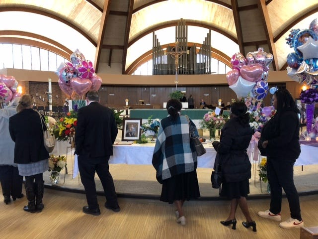 """Mourners look at photos during the memorial service for Amarah """"Jerica"""" Banks and her daughters,  Zaniya Ivery, 5, and Camaria Banks, 4."""