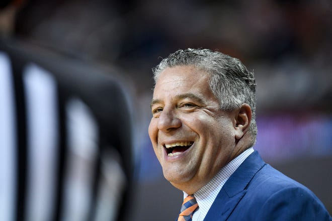 Auburn head coach Bruce Pearl smiles at an official during the first half of an NCAA college basketball game against Tennessee Saturday, Feb. 22, 2020, in Auburn, Ala.