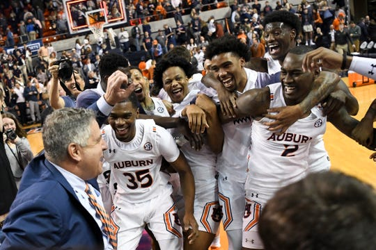Auburn players celebrate with Auburn head coach Bruce Pearl after a win over Tennessee in an NCAA college basketball game Saturday, Feb. 22, 2020, in Auburn, Ala. (AP Photo/Julie Bennett)