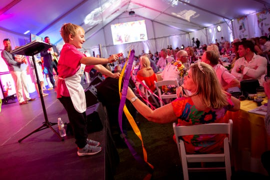 Connor O'Neal, left, plays with ribbon with Paula Pala during the 12th annual Southwest Florida Wine & Food Fest at the Hyatt Regency Coconut Point Resort & Spa in Bonita Springs on Saturday, February 22, 2020.