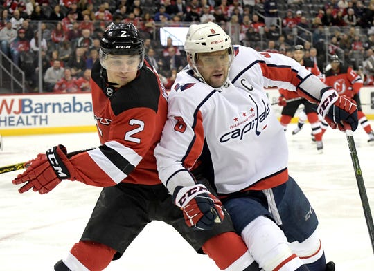 Washington Capitals left wing Alex Ovechkin (8) and New Jersey Devils defenseman Colton White (2) chase after the puck during the first period of an NHL hockey game Saturday, Feb. 22, 2020, in Newark, N.J.