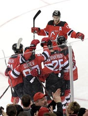 New Jersey Devils defenseman Damon Severson (28) celebrates with teammates after his goal during the third period of an NHL hockey game against the Washington Capitals Saturday, Feb. 22, 2020, in Newark, N.J.