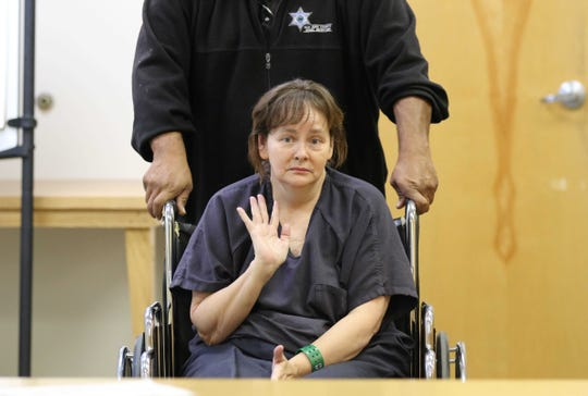 Martha Crouch waves to family members before her preliminary hearing in Aztec Magistrate Court on July 11 in Aztec.
