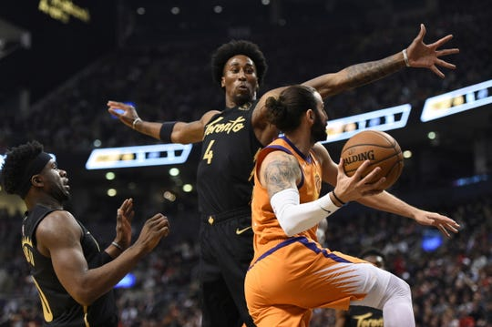 Toronto Raptors forward Rondae Hollis-Jefferson (4) defends against Phoenix Suns guard Ricky Rubio during the first half of an NBA basketball game Friday, Feb. 21, 2020, in Toronto. (Frank Gunn/The Canadian Press via AP)