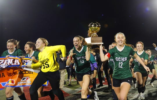 Gilbert Christian's Hannah Burke (12) and Landyn Lovelady (13) carry their 3A State Championship trophy to their schools student section after defeating Sahuarita 1-0 at Williams Field High School in Gilbert, Ariz. on Feb. 21, 2020.