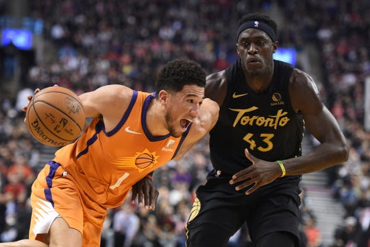 Phoenix Suns guard Devin Booker (1) moves around Toronto Raptors forward Pascal Siakam (43) during the first half of an NBA basketball game Friday, Feb. 21, 2020, in Toronto. (Frank Gunn/The Canadian Press via AP)