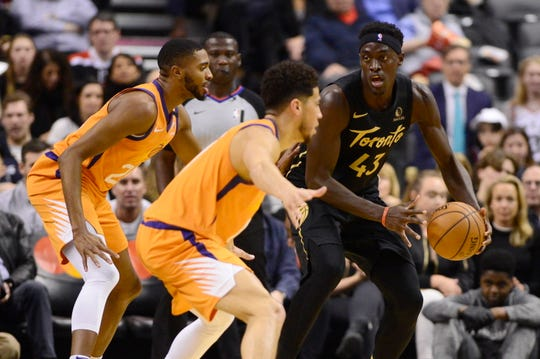Toronto Raptors forward Pascal Siakam (43) works against two Phoenix Sun defenders during the first half of an NBA basketball game Friday, Feb. 21, 2020, in Toronto. (Frank Gunn/The Canadian Press via AP)