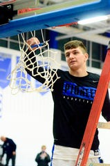 Croswell-Lexington's Jake Noll cuts down the net after beating Algonac and winning the Blue Water Area Conference championship in boys basketball on Friday, Feb. 21, 2020.