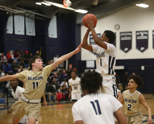 Poughkeepsie's Revelation Garriga takes a jump shot over Beacon's Shane Green during Friday's playoff game on February 21, 2020.