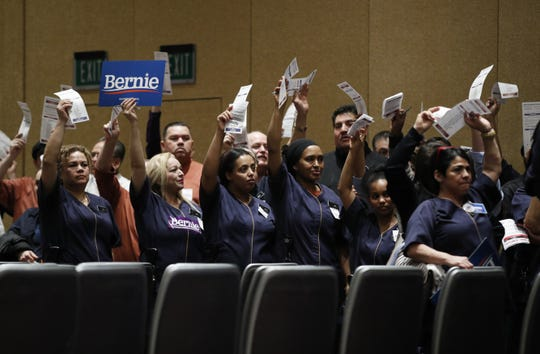 Casino workers hold up presidential preference cards as they support Democratic presidential candidate Sen. Bernie Sanders, I-Vt., during a presidential caucus at the Bellagio hotel-casino, Saturday, Feb. 22, 2020, in Las Vegas. (AP Photo/John Locher)