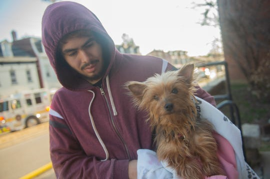 Antonio Martinez holds Princess outside the 4-house fire along the 600 block of E. Philadelphia Street in York on Saturday, Feb. 22, 2020. Princess was inside 628 E. Philadelphia St. when the fire began, crews were able to rescue her. Martinez is one of several persons who have been displaced in the fire.