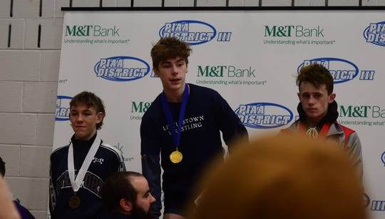 Littlestown's Connor Brown accepts his gold medal for winning the 113-pound District 3 Class 2A title at Central Dauphin East Saturday.
