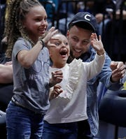 Golden State Warriors' Steph Curry laughs with his daughters, Riley Curry, left, and Ryan Curry, during halftime of an NCAA college basketball game between Oregon and California on Feb. 21, 2020, in Berkeley, Calif.