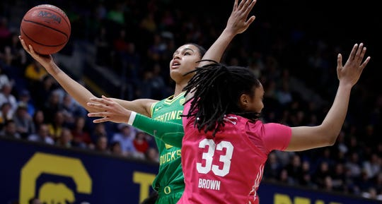 Oregon's Satou Sabally, left, shoots past California's Jaelyn Brown (33) in the first half of an NCAA college basketball game Feb. 21, 2020, in Berkeley, Calif.
