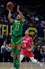 Oregon's Minyon Moore, left, shoots past California's Leilani McIntosh (1) in the first half of an NCAA college basketball game  Feb. 21, 2020, in Berkeley, Calif.