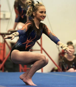 San Angelo Central High School's Hailey Smith flashes a smile during her floor exercise routine in a home gymnastics meet against Saginaw on Saturday, Feb. 22, 2020.