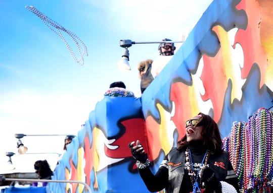 Vivian Andrews throws beads from a float during the Krewe of Gemini Parade Saturday afternoon, February 22, 2020.