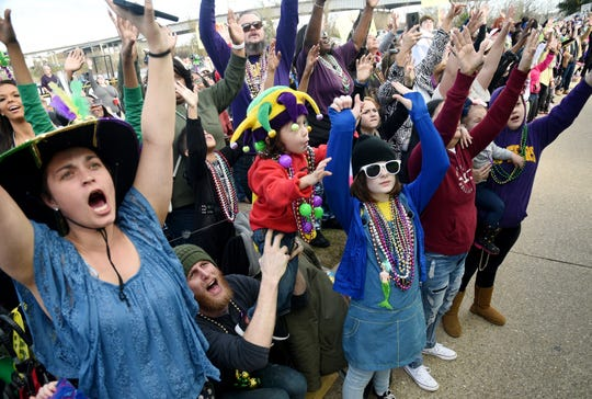 People scream for beads during the Krewe of Gemini Parade Saturday afternoon, February 22, 2020.