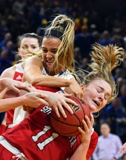 USD's Monica Arena and SDSU's Lindsey Theuninck wrestle for the ball during their game on Saturday, Feb 22, at Frost Arena in Brookings.