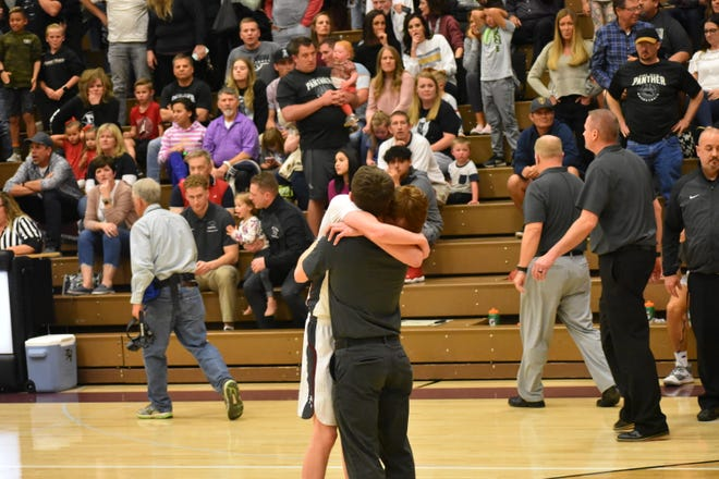 "Jared Koller hugs an assistant coach after the Panthers' heart-breaking loss. Koller was the most emotional describing his love for his teammates: ""I don't wanna grow up. It's just sad. I love all my teammates. I moved here in sixth grade with this team and Suds, Jared Sudweeks, is my best friend."""