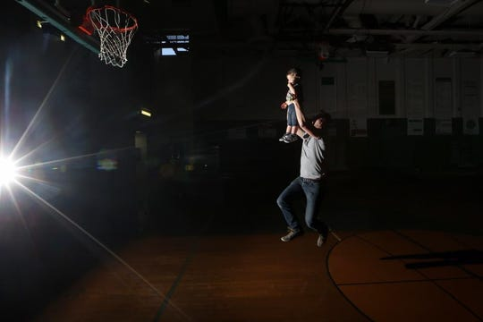 Democrat prep sports editor Brian Miller practices an All-Big Bend basketball photo shoot using his 2-year-old son Avett.