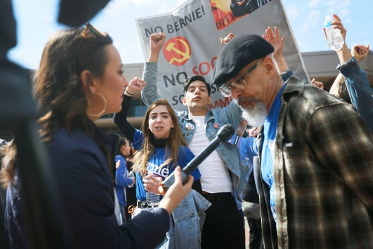 "Saul Armando Fontes, and a volunteer who did not want to give her name, and Pro-Trump supporters with ""No Bernie"" signs cheer behind KFOX reporter Mills Hayes as she interviews someone before the Bernie Sanders rally Saturday, Feb. 22, at the Abraham Chavez Theatre in El Paso."