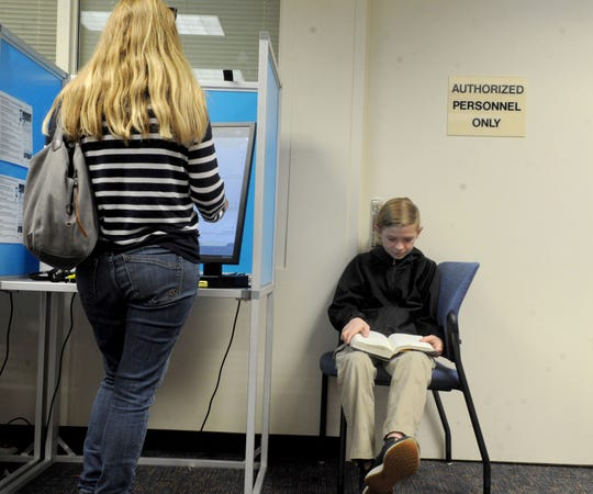 Shanna Farley-Judkins, of Ventura, votes on Feb. 22, 2020, at the Ventura County Government Center elections office while her son Chase waits.
