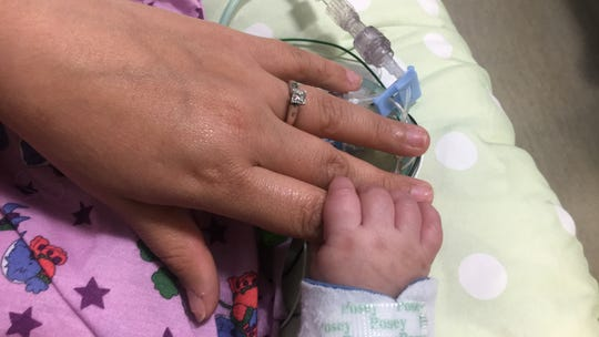 Janessa Torres grasps her mother's hand. The baby  was born with her intestines on the outside of her abdomen. They have been returned to her belly but she remains at Cedars-Sinai Medical Center in Los Angeles.