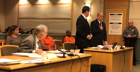 Former Millville police Officer Jeffrey E. Profitt (right) here rises in Superior Court on Friday to defend his official conduct. Profitt was sentenced to probation and a suspended jail term for aggravated assault on a 68-year-old man. He stands next to his attorney, Michael L. Testa Sr. At left, Cumberland County First Assistant Prosecutor Harold B. Shapiro reacts to his opening statement.
