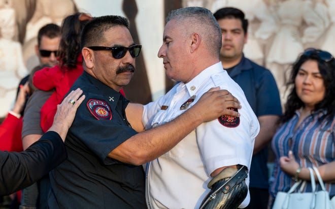 Tulare Fire Chief Luis Nevarez, right, comforts Mitchell Sandoval from the Porterville Fire Department during a memorial service for two firefighters killed in Tuesday's fire at the library.