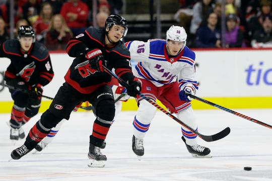 Carolina Hurricanes center Sebastian Aho, left, of Finland, skates for the puck against New York Rangers center Ryan Strome (16) during the second period of an NHL hockey game in Raleigh, N.C., Friday, Feb. 21, 2020.