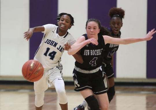 John Jay-East Fishkill's Stephanie Jean-Baptist (14) and New Rochelle's Nora Fitzgerald (4) fight for a loose ball during their 54-43 win over New Rochelle in the opening round of the Class AA girls basketball tournament at New Rochelle High school in New Rochelle on Saturday, February 22, 2020.
