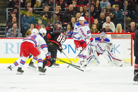 Feb 21, 2020; Raleigh, North Carolina, USA;  Carolina Hurricanes center Martin Necas (88) shot is blocked by New York Rangers defenseman Tony DeAngelo (77) during the first period at PNC Arena.