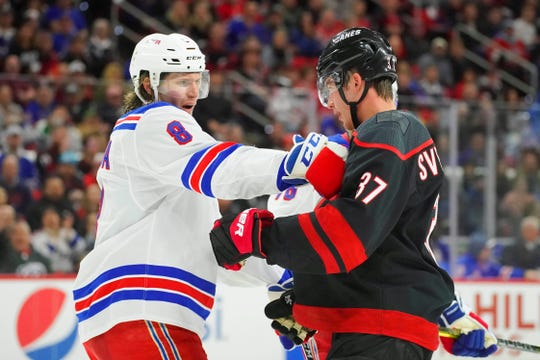 Feb 21, 2020; Raleigh, North Carolina, USA;  Carolina Hurricanes right wing Andrei Svechnikov (37) and New York Rangers defenseman Jacob Trouba (8) battle during the second period at PNC Arena.