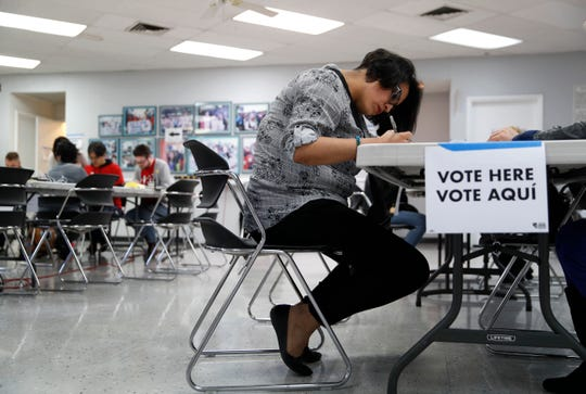 FILE - In this Feb. 15, 2020, file photo, a woman votes at an early voting location at the culinary workers union hall  in Las Vegas. Nevada Democrats are hoping to avoid a repeat of the chaos that ensnared the Iowa caucuses, as voters gather across the Silver State on Saturday to make their presidential preferences known.  (AP Photo/John Locher, File)