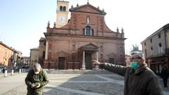 People wear masks as they stand in front of the San Biagio church in Codogno, near Lodi, Northern Italy, on Feb. 22, 2020. A dozen towns in northern Italy are on effective lockdown after the new virus linked to China claimed the first of two fatalities in Italy and sickened an increasing number of people.