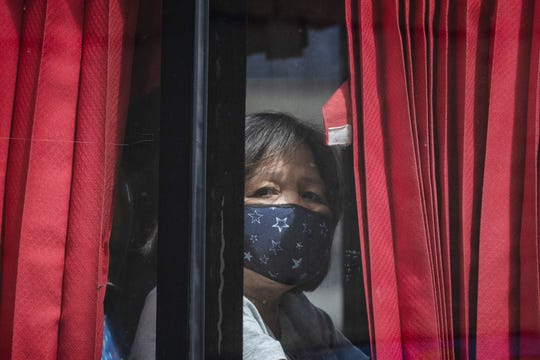 A woman riding a bus wears a face mask in this Feb. 21 file photo, in Quezon City, Metro Manila. Philippine President Rodrigo Duterte Thursday night announced restrictions to travel and quarantine of Metro Manila.