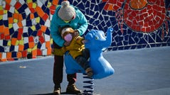 Amidst coronavirus fears, a woman wearing a face mask puts a mask on a boy as he plays at a playground in Beijing on Saturday, Feb. 22 2020.
