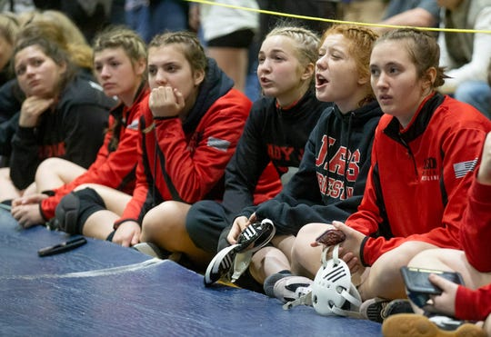 Female wrestlers in New Jersey cheer on their teammates during a recent regional meet. South Dakota is now considering add girls wrestling as a high school sport.