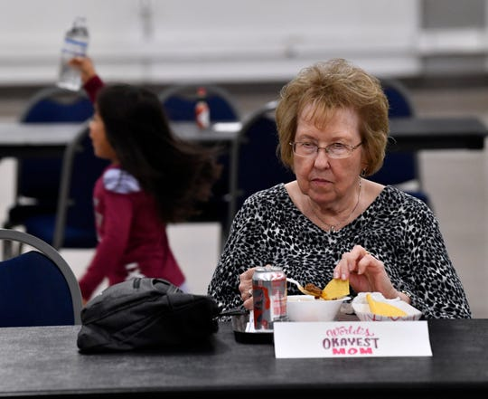 Pat Gazaille eats her chili as a child runs by behind her with a bottle of water Saturday. The place marker in front of her is one of the sponsors for the annual Kiwanis Chili Day & Auction. World's Okayest Mom is a local nonprofit assisting mothers in need.