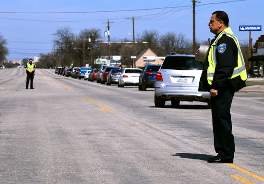 "Officer Pat Salas (right) and Sgt. Jason Moran of the Coleman Police Department stand watch as motorists drive to Coleman City Cemetery to bury Howard ""Coach"" Childress Friday."