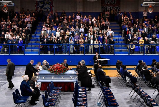 "Attendees stand to cheer and applaud Howard ""Coach"" Childress as his casket is wheeled out of the Coleman High School gymnasium Friday. Childress died Feb. 13, and was an educational icon in the community for more than 60 years."